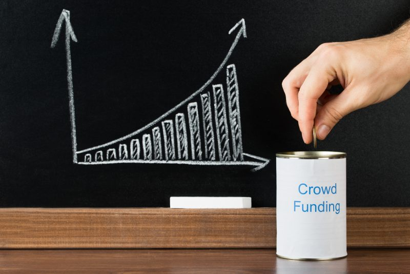 Close-up Of A Person Inserting Coin In Crowd Funding Can In Front Of Blackboard Showing Graph